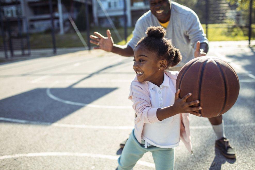 Girl learning to play basketball