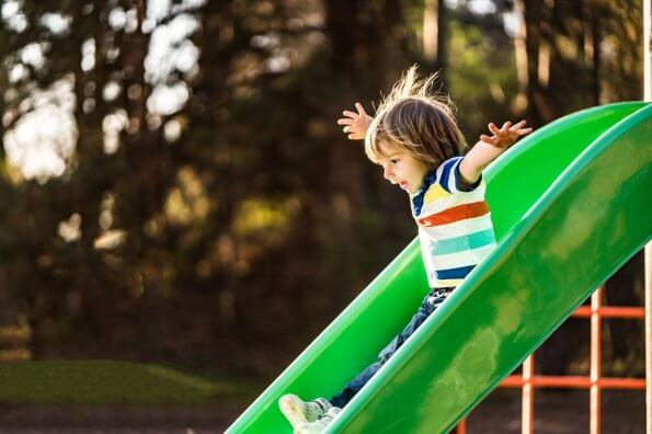 child going down slide backyard play set